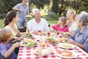 Three Generation Family Enjoying Barbeque In Garden Together