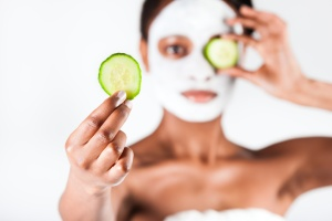 Young African woman in Studio doing body care with refreshing cucumber facial mask for young and beautiful skin and relaxation
