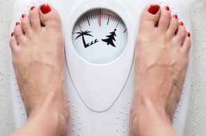 Female feet on bathroom scale with symbols for loosing weight before summer